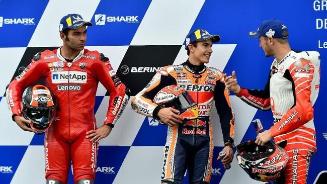 Marc Marquez bersama Danilo Petrucci (kiri) dan Jack Miller (kanan) sebagai tiga pebalap tercepat dalam sesi kualifikasi. Marquez membukukan pole position ke-55 dalam karier di MotoGP menyamai Valentino Rossi. (JEAN-FRANCOIS MONIER / AFP)