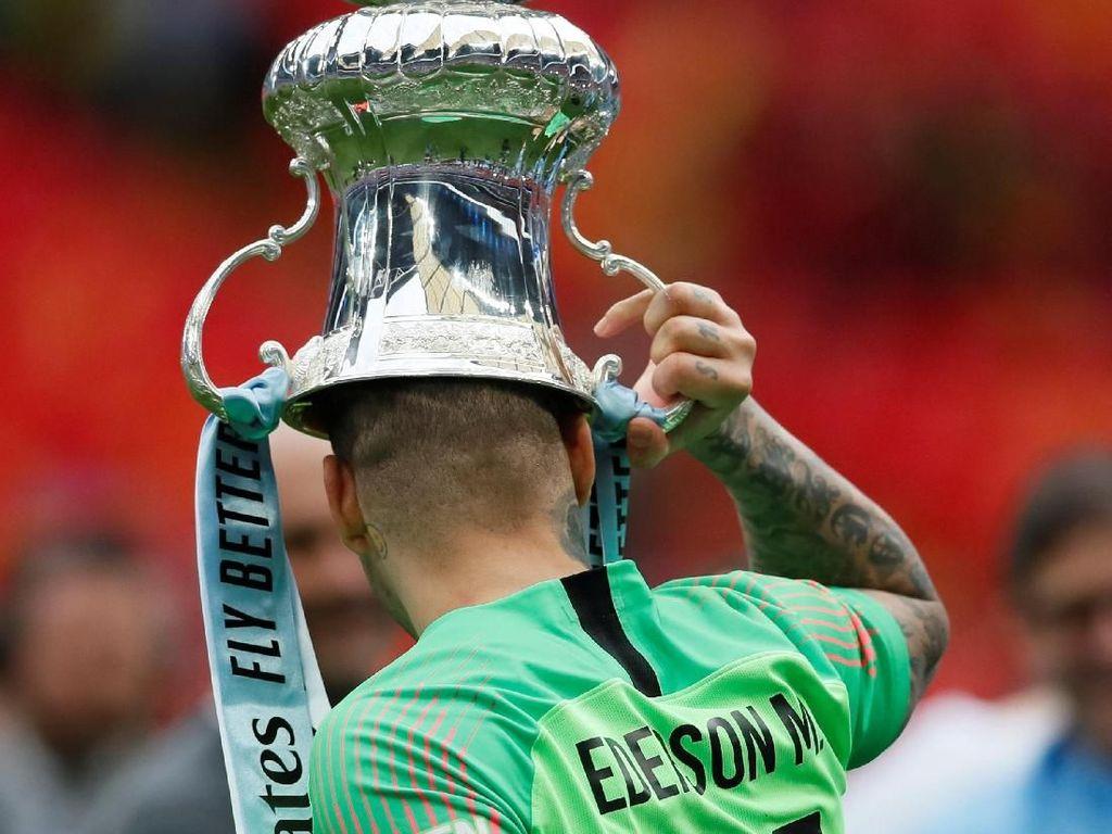Ederson Moraes adalah kiper yang menenteng turun trofi Piala FA dari podium penyerahan. Sebelum dia membawanya sambil meletakkan di kepala. (Foto: David Klein/Reuters)