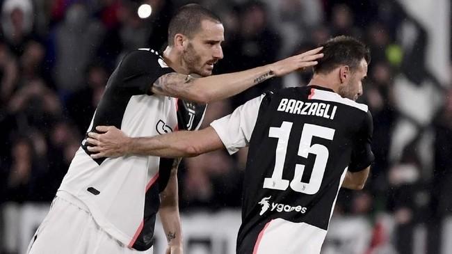 Andrea Barzagli mendapat ucapan selamat dari Leonardo Bonucci. Barzagli bermain di 281 pertandingan untuk Juventus dan merebut delapan Scudetto, empat Coppa Italia, dan empat Piala Super Italia. (Marco Bertorello / AFP)