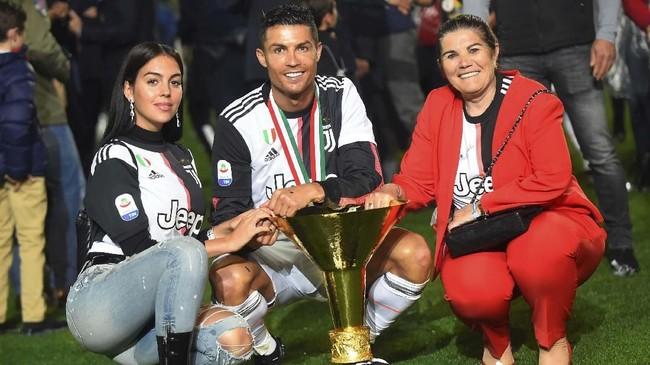 Cristiano Ronaldo berpose bersama sang pacar, Georgina Rodriguez, dan ibunda, Dolores Aveiro, dengan trofi Liga Italia. Ronaldo jadi pemain pertama yang juara di Liga Italia, Liga Spanyol, dan Liga Inggris. (REUTERS/Massimo Pinca)