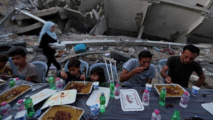 Palestinians break their fast by eating the Iftar meals during the holy month of Ramadan, near the rubble of a building recently destroyed by Israeli air strikes, in Gaza City May 18, 2019. REUTERS/Ibraheem Abu Mustafa