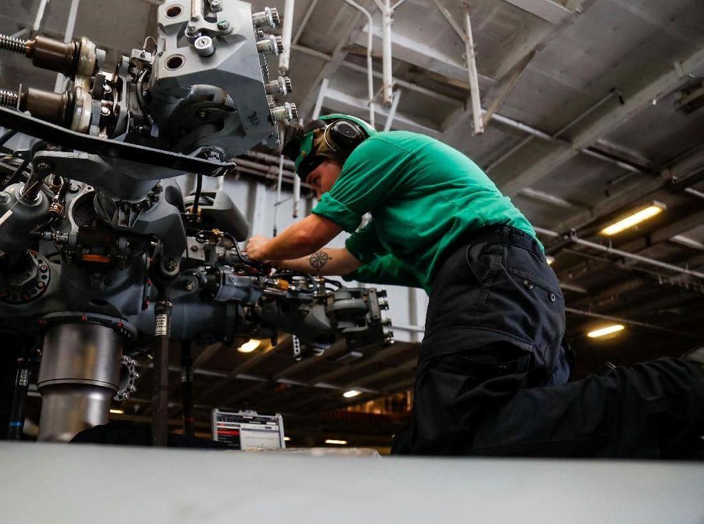 Tampak mekanik sedang memasang komponen di helikopter MH-60R Sea Hawk. Foto: Reuters