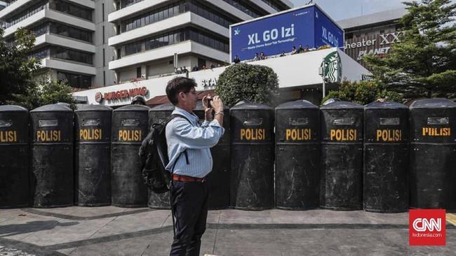 Orator melontarkan pernyataan sementara satuan polisi menggunakan tameng menjaga agar massa tak merangsek ke dalam gedung Bawaslu RI, Jakarta Pusat, 21 Mei 2019. (CNN Indonesia/Safir Makki)