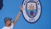 Pep Guardiola melambaikan tangan kepada fan Man City di atas panggung perayaan juara. (Action Images via Reuters/Lee Smith)