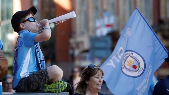 Seorang anak mengenakan kostum replika Manchester City meniup terompet menyambut kedatangan skuat The Citizens. (Action Images via Reuters/Carl Recine)