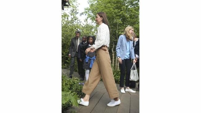 Kate terlihat santai dengan atasan putih M.i.h Jeans, kulot cokelat Massimo Dutti, belt cokelat, dan sepatu Superga. (Yui Mok/Pool via REUTERS)