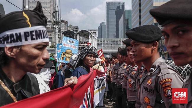 Massa pengunjuk rasa di seberang kantor Bawaslu RI berhadap-hadapan dengan polisi yang menjaga keamanan jalannya aksi. (CNN Indonesia/Safir Makki)
