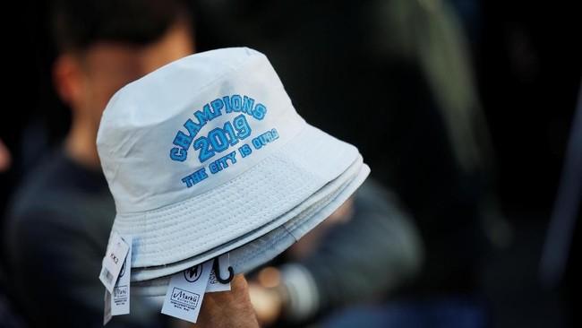 Topi jenis bucket hat menjadi salah satu suvenir yang dijual dalam perayaan juara Manchester City. (Action Images via Reuters/Carl Recine)