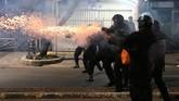 Tembakan gas air mata dibalas massa dengan lemparan batu dan petasan. Namun tidak menyurutkan langkah petugas untuk mendesak pelaku yang mundur hingga Pasar Tanah Abang.(BAY ISMOYO/AFP)