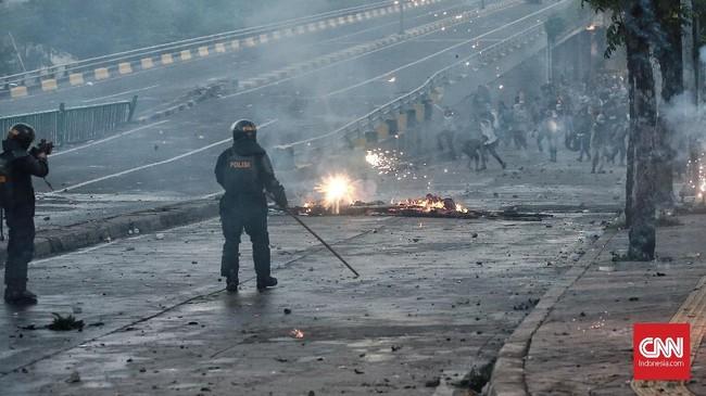 Perlawanan sengit dilancarkan massa. Mercon mereka seolah-olah tak habis-habis. Sementara gas air mata polisi semakin menipis. Walhasil polisi akhirnya juga mengombinasikan gas air mata dan mercon untuk mengusir massa. (CNN Indonesia/Andry Novelino)