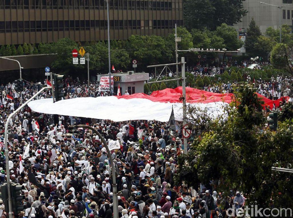 Dalam aksi demo yang digelar di depan gedung Bawaslu tersebut massa nampak membentangkan bendera merah putih berukuran raksasa.