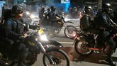 Pasukan bermotor polisi juga sempat dikerahkan untuk mengurai massa. Hal ini efektif namun massa kembali berkumpul di tempat lain. (BAY ISMOYO/AFP)