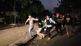 Polisi dan warga menangkap seorang yang diduga menjadi provokator pembakaran mobil di Komplek Asrama Brimob, Petamburan, Jakarta, Rabu (22/5).