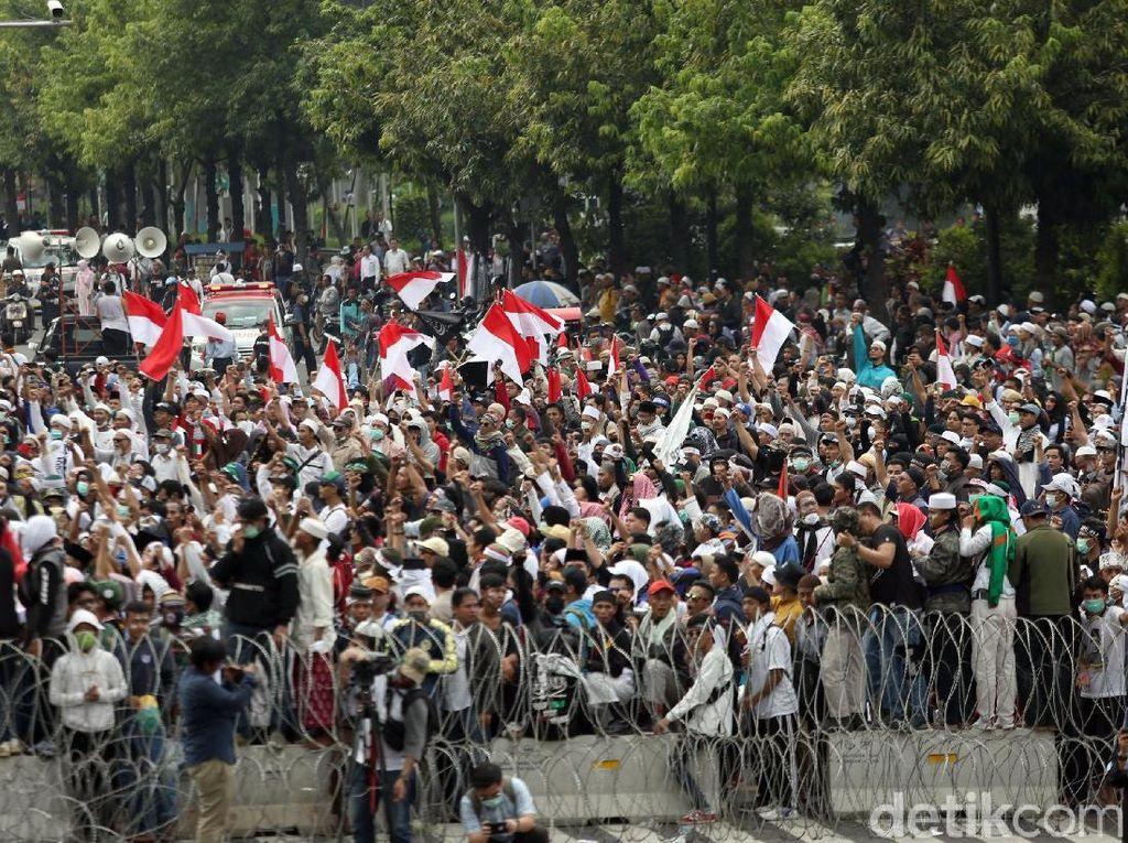 Massa juga nampak mengibarkan bendera merah putih saat melakukan aksi demo di depan gedung Bawaslu, Jakarta.
