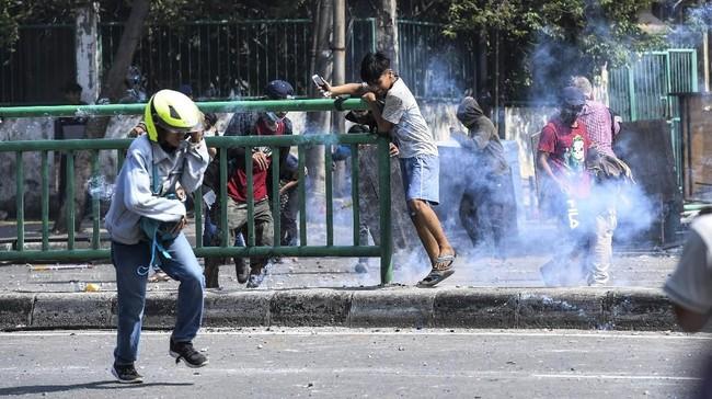 Massa berhamburan ketika ditembakan gas air mata saat kerusuhan terjadi di Jalan Jati Baru Raya, Tanah Abang, Jakarta, Rabu (22/5/2019). (ANTARA FOTO/Hafidz Mubarak A)