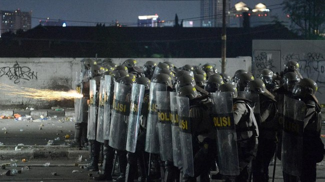 Personel kepolisian menembakkan gas air mata pada massa aksi di Jalan Brigjen Katamso, Slipi, Jakarta, Rabu (22/5). (ANTARA FOTO/M Risyal Hidayat/wsj).