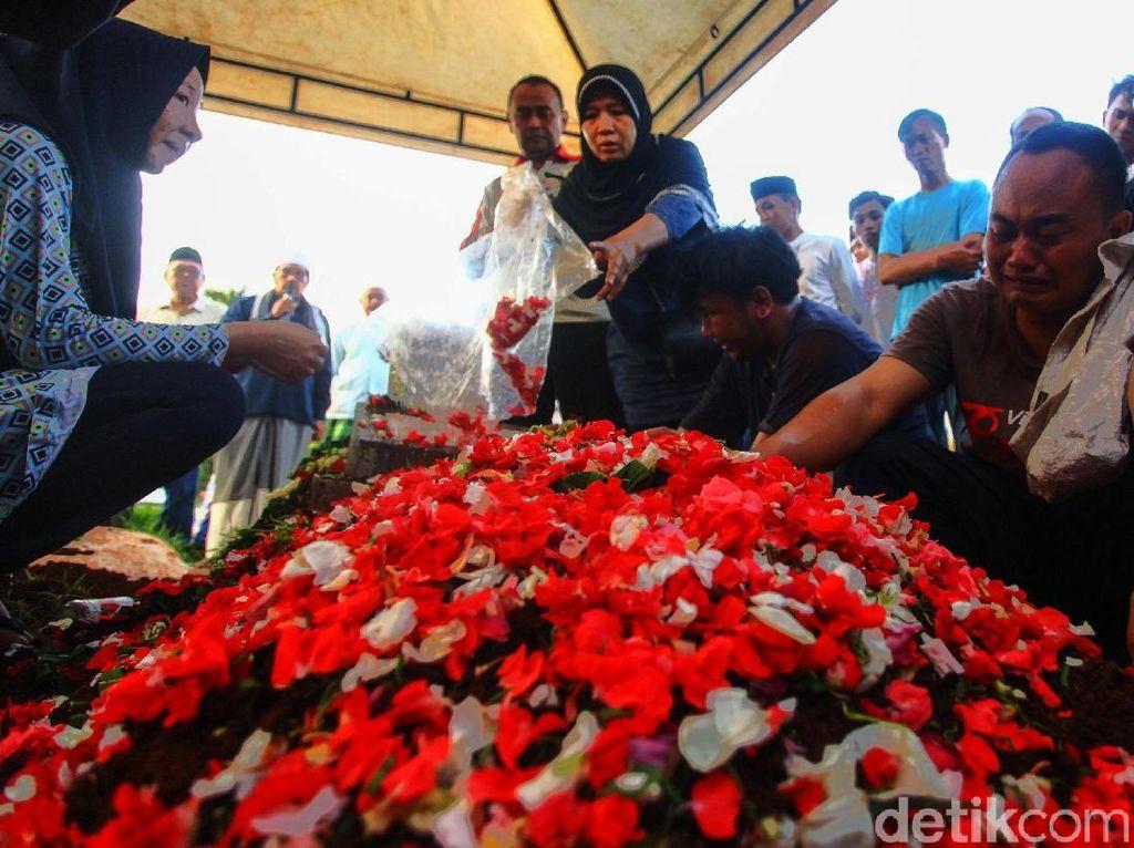 Isak tangis dari keluarga mengiringi proses pemakaman.