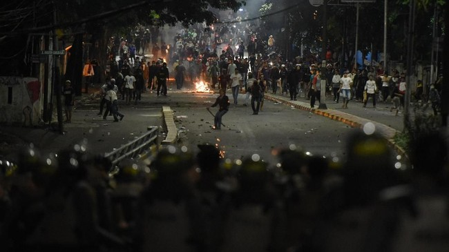 Personel kepolisian berjalan keluar dari barisan barikade saat kericuhan Aksi 22 Mei yang terjadi di Jalan Brigjen Katamso, Slipi, Jakarta, Rabu (22/5/). (ANTARA FOTO/M Risyal Hidayat/wsj).