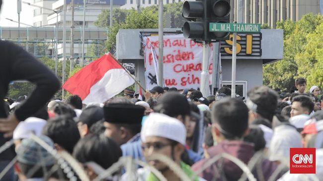 Massa Membentangkan Bendera Merah Putih di Depan Bawaslu