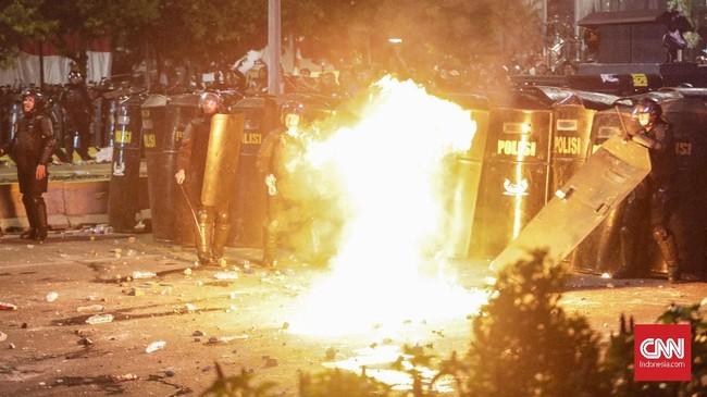Lemparan gas air mata dibalas oleh massa dengan petasan dan benda tumpul lain. Situasi semakin mencekam setelah muncul sejumlah titik api tak jauh dari lokasi kerusuhan.(CNN Indonesia/Adhi Wicaksono)