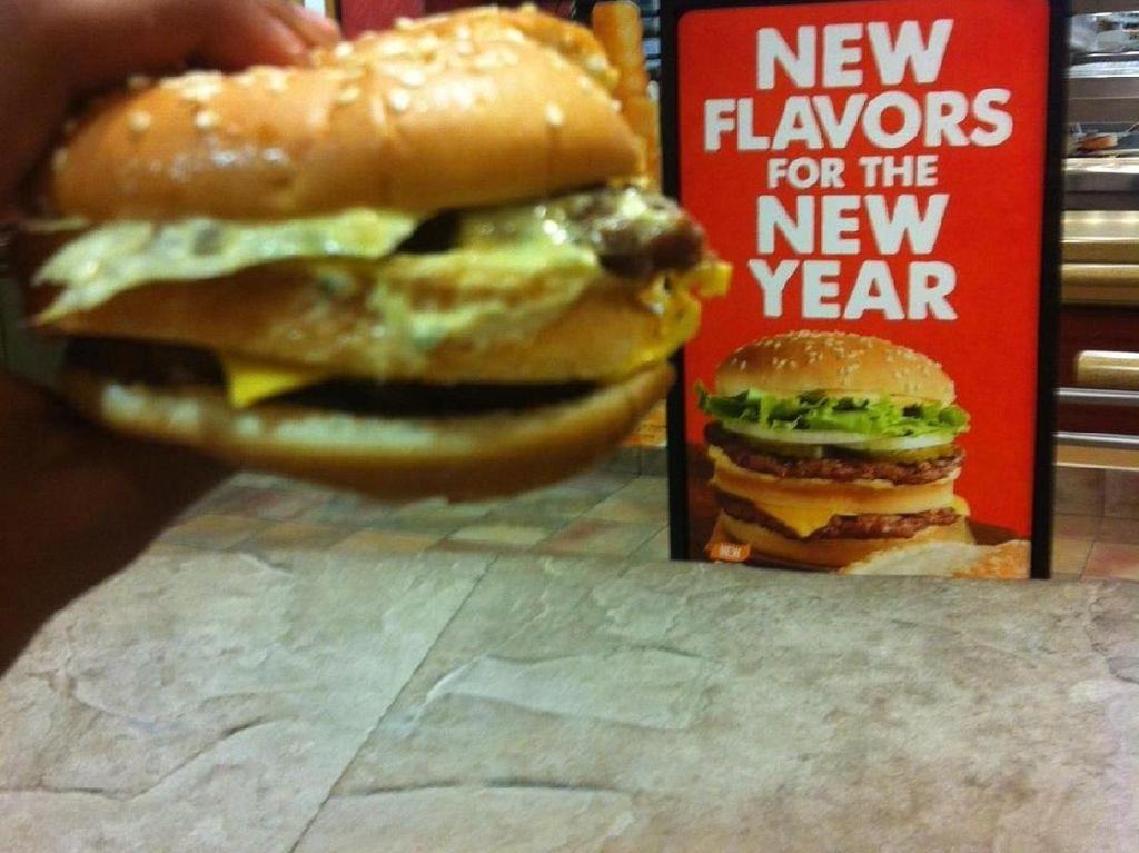Pesan burger di salah satu gerai restoran cepat saji, yang datang justru burger tipis dengan isian yang keluar tak beraturan. Beda jauh dari papan iklan menu yang ada. Foto: Istimewa