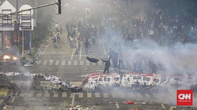 Kerusuhan terjadi sekitar pukul 18.20 WIB. Polisi merangsek ke kerumunan massa aksi dengan melepaskan tembakan gas air mata. Tindakan tegas ini dipicu oleh lemparan botol plastik dari arah massa aksi ke aparat keamanan. (CNN Indonesia/Adhi Wicaksono)