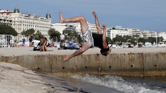 Seorang pria melakukan salto, berjungkir balik di udara, di Pantai Croisette, Cannes, Prancis. (Reuters/Eric Gaillard)