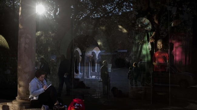 Seorang perempuan menulis, dengan refleksi orang-orang di Biara Sant Cugat, Catalonia, Spanyol. (AP/Emilio Morenatti)
