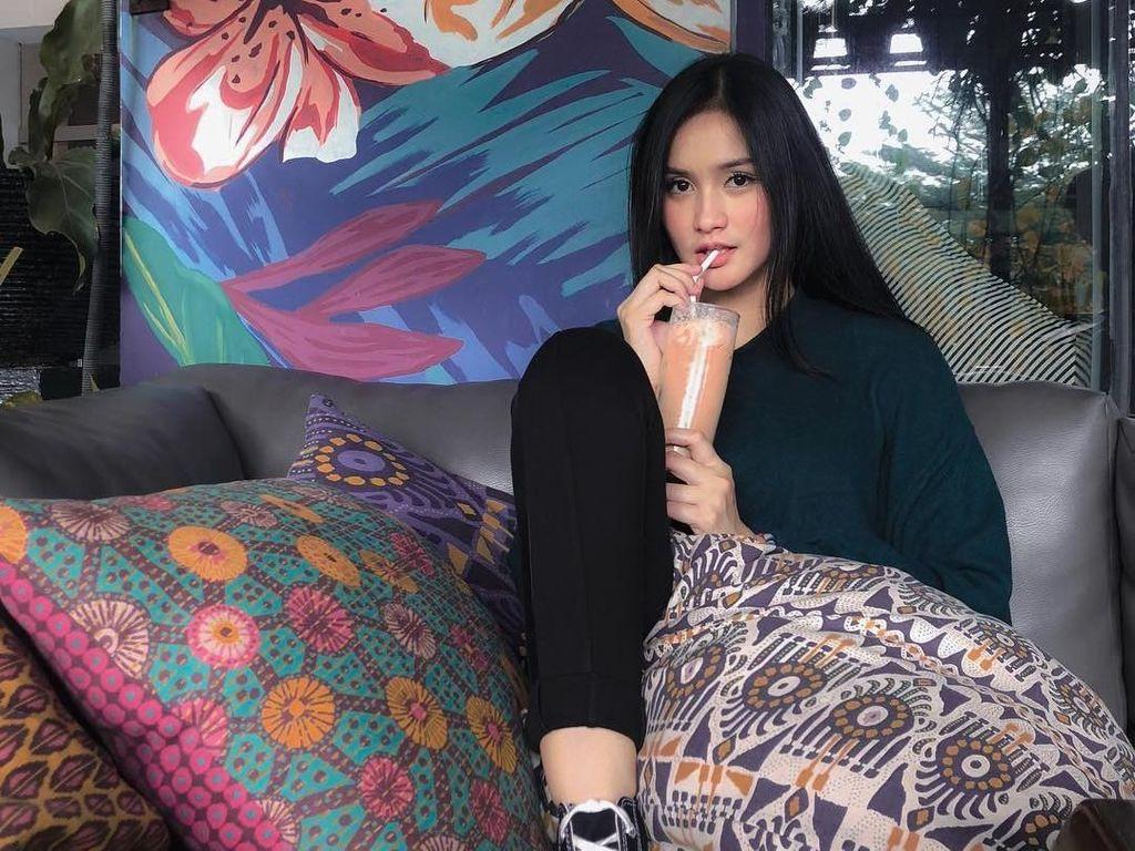Jangan salah fokus sama kecantikan Isel, hihihi. Ini pose santainya di kafe sambil menyeruput minuman. Foto: Instagram iselfricella/miqdadsy