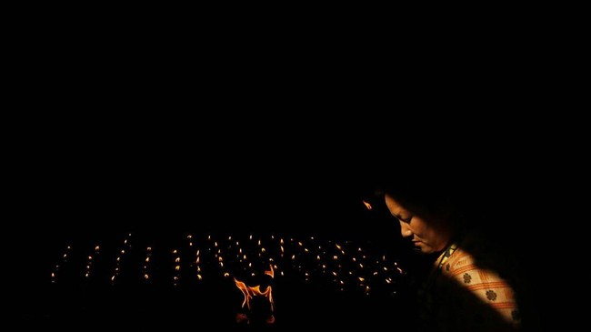 Seorang perempuan Buddha menyalakan lilin dalam Festival Buddha Purnima atau Buddha Jayanti di Kathmandu, Nepal. Festival ini menandai tiga fase kehidupan Buddha; kelahiran, pencerahan, dan mencaai nirwana. (AP/Niranjan Shrestha)