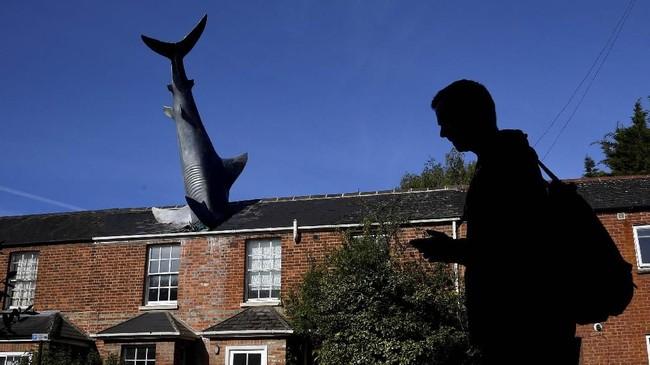 Seorang pria melewati patung