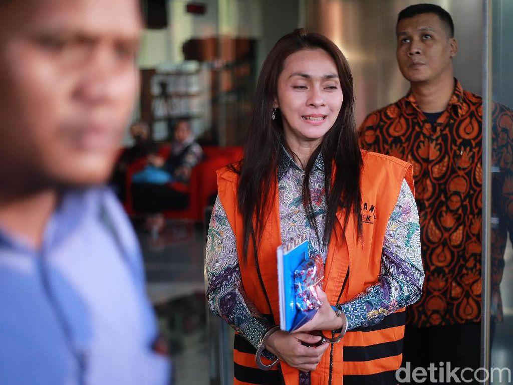 Sri Wahyumi keluar gedung KPK dengan mengenakan kemeja putih lengan panjang, rompi tahanan warna oranye, dan tangan diborgol.