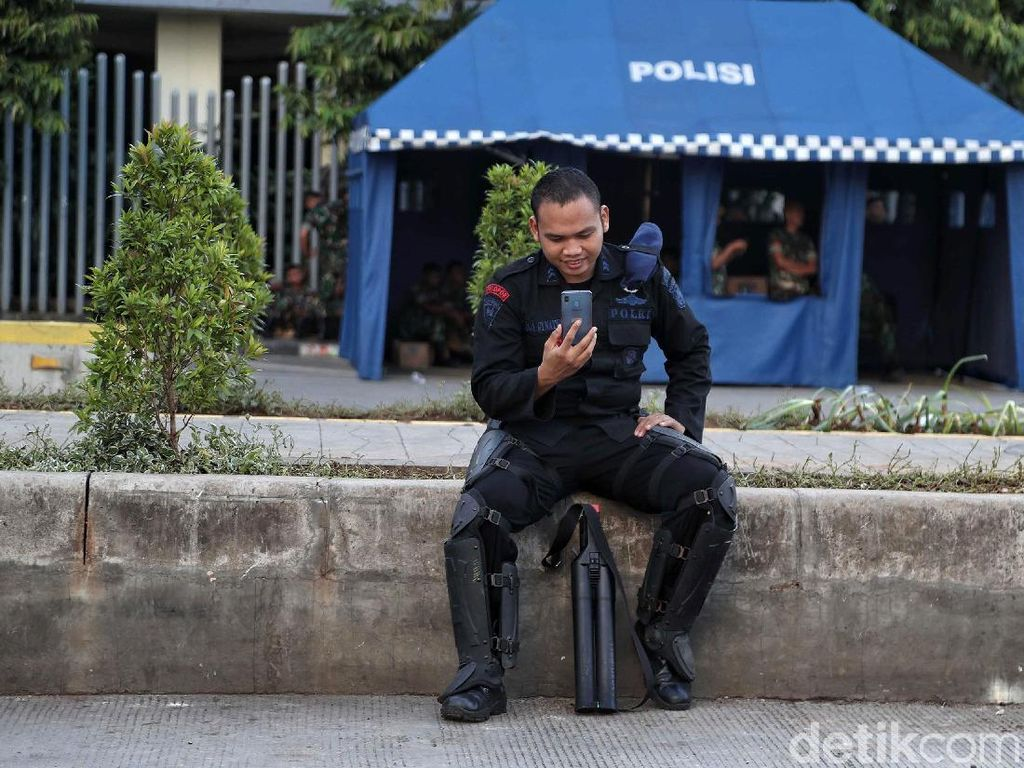 Seorang anggota Brimob beristirahat sejenak di sela-sela tugasnya mengamankan kawasan Bawaslu.