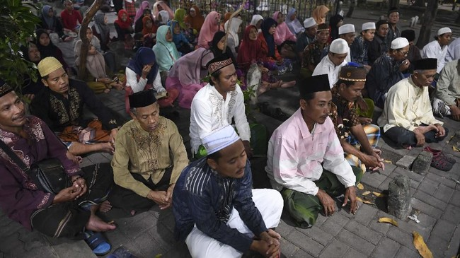 Pria dan wanita berdoa di Makam Sunan Ampel Surabaya, Jawa Timur. (ANTARA FOTO/Zabur Karuru)