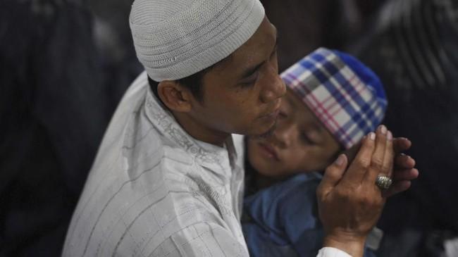 Seorang ayah menggendong anaknya yang tertidur lelap saat mengunjungi Makam Sunan Ampel Surabaya, Jawa Timur. (ANTARA FOTO/Zabur Karuru)