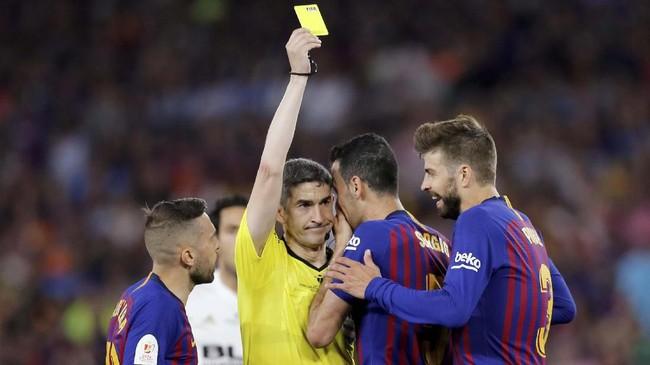 Gelandang Barcelona Sergio Busquets berbisik kepada wasit Alberto Undiano Mallenco setelah menerima kartu kuning. (REUTERS/Marcelo del Pozo)