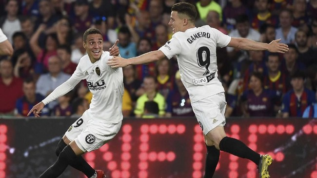 Memasuki menit ke-33 Valencia berhasil menggandakan keunggulan setelah sundulan Rodrigo Moreno (kiri) menggetarkan gawang Barcelona. (JOSE JORDAN / AFP)