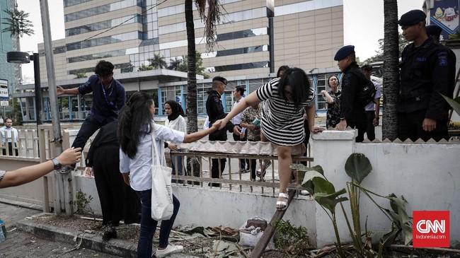 Karyawan yang bekerja di kawasan MH Thamrin melompati pagar saat jam istirahat kerja di mal Sarinah, Jakarta, Senin, 27 Mei 2019. Mal tertua se-Indonesia itu berada tepat di seberang Gedung Bawaslu RI. (CNNIndonesia/Safir Makki)