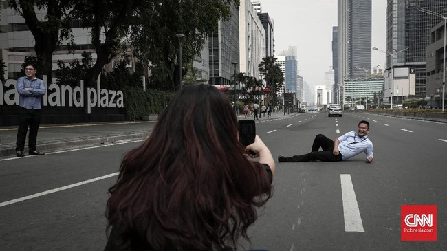 Karyawan menyempatkan diri berfoto di ruas jalan yang sepi di kawasan MH Thamrin, Jakarta, Senin, 27 Mei 2019. Hari ini merupakan hari pertama kerja setelah diliburkan pada 21 sampai 24 Mei pekan lalu. (CNNIndonesia/Safir Makki)