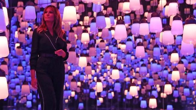 Dalam kunjungannya bersama istri PM Jepang, Akie Abe di Mori Building Digital Art Museum, Melania memakai jumpsuit dari Loro Piana seharga US$3.500 yang dipadukan dengan sepatu flat. (REUTERS/Athit Perawongmetha)