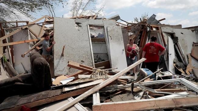 Namun, sebagian warga tak begitu peduli dengan banjir itu saat ini. Mereka hanya ingin selamat dari sapuan tornado. (Reuters/Kyle Grillot)