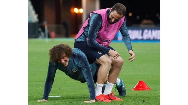 David Luiz (bawah) tersenyum meski tengah diduduki Gonzalo Higuain. Namun dalam beberapa berita di Eropa, keduanya juga terlibatperselisihan di latihan tersebut.(REUTERS/Maxim Shemetov)