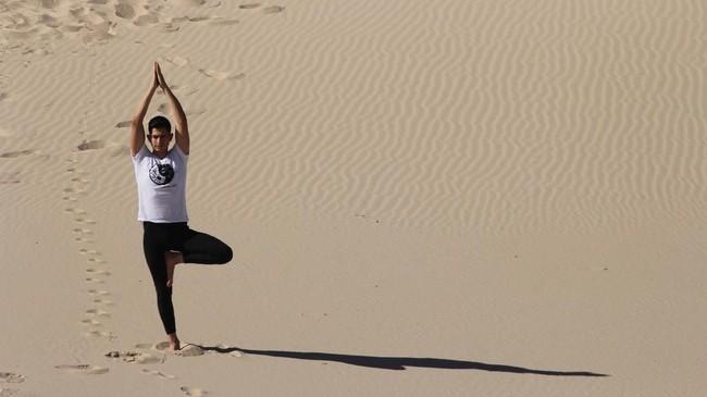 Banyak orang yang menghadiri kelas yoga selama pertemuan yang diselenggarakan oleh komunitas sistem YSYoga di Samalayuca Dune Fields di Juarez, Meksiko. (Photo by Herika MARTINEZ / AFP)