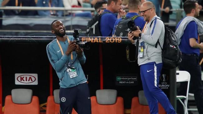 BekAntonio Ruediger tersenyum lebar sembari memegang kamera. Ruediger tampak tengah belajar memotret bersama ofisial Chelsea. (REUTERS/Maxim Shemetov)