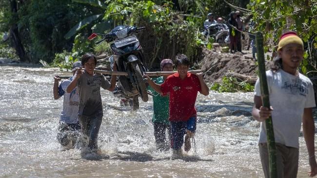 Warga mengungsi ke tempar-tempat aman membawa harta benda yang bisa diselematkan. Tampak sejumlah warga memanggul sepeda motor saat menyeberangi arus air banjir bandang yang melanda Desa Tuva, Kecamatan Gumbasa, Kabupaten Sigi. (ANTARA FOTO/Basri Marzuki/wsj).