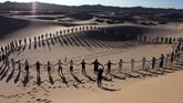 Lebih dari 50 orang mengikuti kelas yoga di padang pasir Samalayuca di Juarez, Chihuahua, Meksiko, pada Sabtu (25/5) lalu. (Photo by Herika MARTINEZ / AFP)