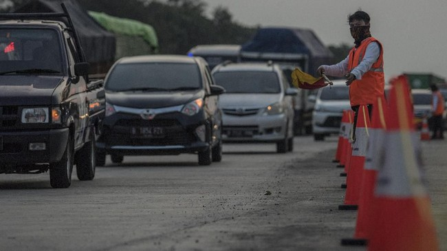 Petugas membantu mengarahkan kendaraan yang memasuki Gerbang Tol Cikampek Utama, CIkampek, Jawa Barat, Rabu (29/5/2019). Saat mudik Lebaran, Korlantas Polri memberlakukan kebijakan jalur satu arah (one way) untuk kendaraan dari Jakarta menuju arah Jawa Tengah. (ANTARA FOTO/Sigid Kurniawan/ama).