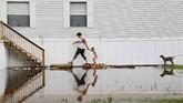 Samantha Karnes dan putranya yang berusia tiga tahun, Anthony Pickett, berjalan ke arah rumah tetangga untuk memeriksa keberadaanya di tengah-tengah banjir karena luapan Sungai Arkansas. (Mike Simons/Tulsa World via AP)