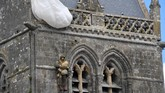 Foto menunjukkan patung prajurit di menara lonceng gereja Sainte-Mere-Eglise, di barat daya Perancis. Patung itu dibuat untuk mengenang John Steele yang tersangkut di menara saat Pertempuran Normandy di Perang Dunia II. (Photo by Damien MEYER / AFP)