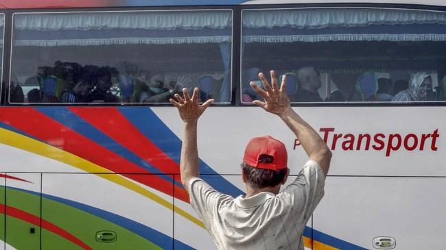 Warga melambaikan tangan kepada sanak keluarganya yang mudik di Terminal Jatijajar, Depok, Jawa Barat, Kamis (30/5/2019). Menurut Badan Pengelola Transportasi Jabodetabek (BPTJ) puncak arus mudik di Terminal Jatijajar diprediksi akhir pekan ini, mulai dari Jumat hingga Sabtu. (ANTARA FOTO/Yulius Satria Wijaya/wsj).